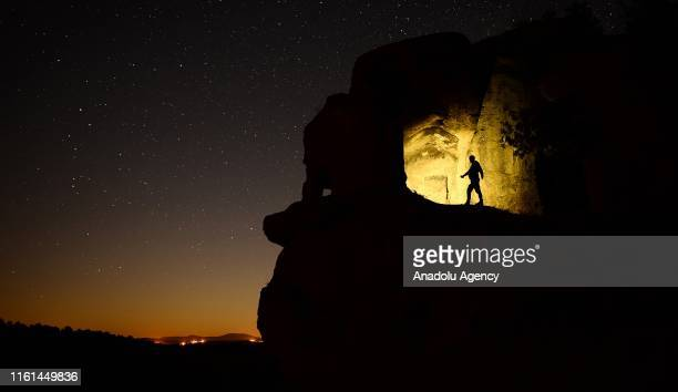 Silhouette of a man standing over a rock with a clear night sky over the ancient city of Mesotimolos in Esme district of Turkey's western Usak...