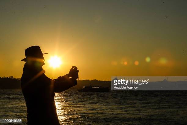 Silhouette of a man taking a photo with a mobile phone is seen during sunset at Salacak shore in Istanbul, Turkey on February 13, 2020.