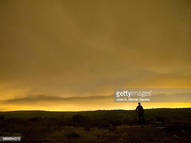 Silhouette of a man to cross-light on the top of a mountain a night of clouds orange color