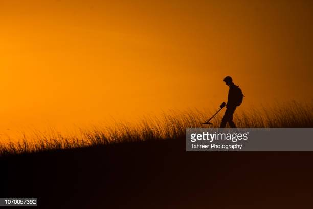 Silhouette of a man using recreational metal detector