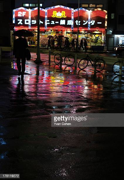 Silhouette of a man walking in the rain at night in Tokyo