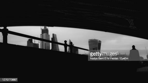 silhouette of a man walking on bridge against sky - in silhouette stock pictures, royalty-free photos & images