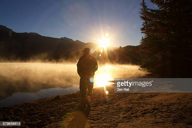 silhouette of a man walking towards a brilliant sunburst on a misty lake at sunrise - zen rial stock photos and pictures