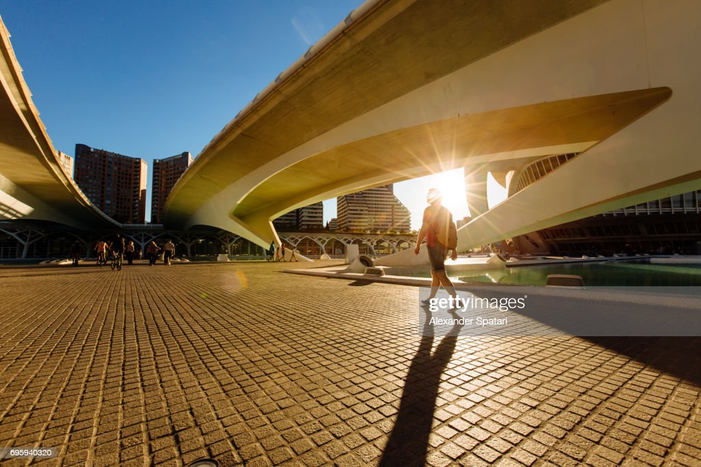 Silhouette of a man walking under the bridge during sunset : ストックフォト