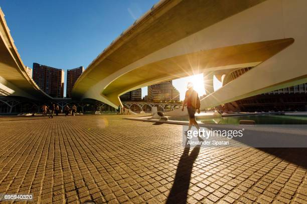 silhouette of a man walking under the bridge during sunset - valencia spanje stockfoto's en -beelden