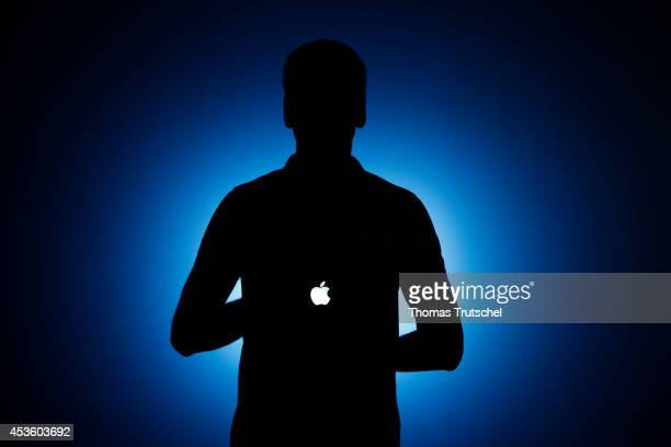 Silhouette of a man who holds an Apple Macintosh laptop on August 06 in Berlin Germany