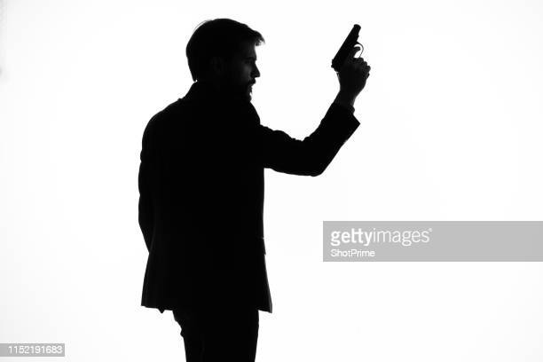 silhouette of a man with a gun in his hands - スパイ ストックフォトと画像