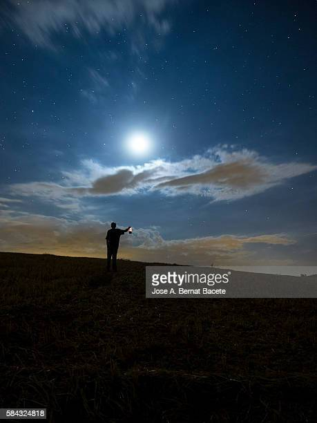 Silhouette of a man with a lantern in hand making signs a night of full moon