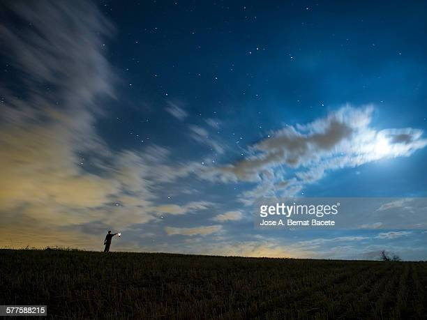 Silhouette of a man with a lantern in the night