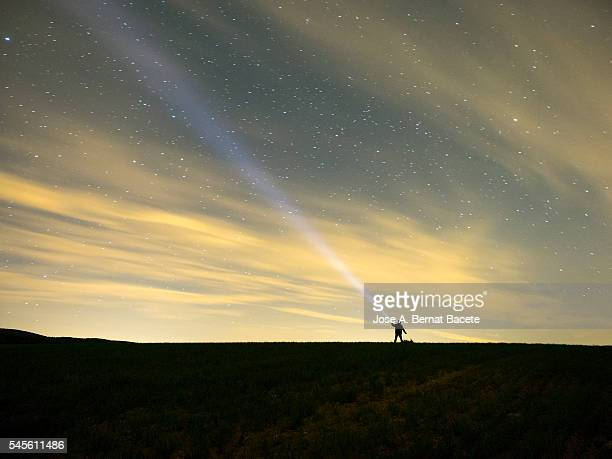 Silhouette of a man with a lantern projecting a bundle of light on the sky during the night in the field