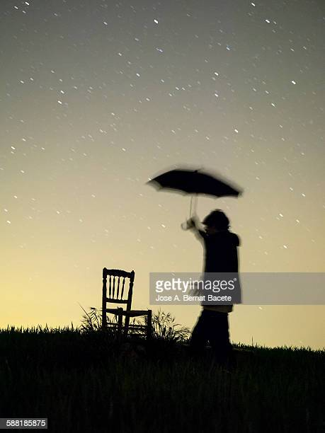 Silhouette of a man with an umbrella in the night