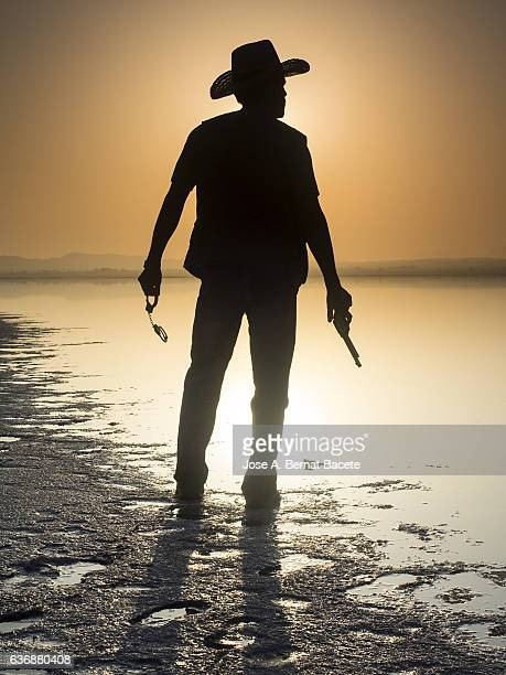 silhouette of a man with cowboy clothes and pistoala front of a lake - 保安官 ストックフォトと画像