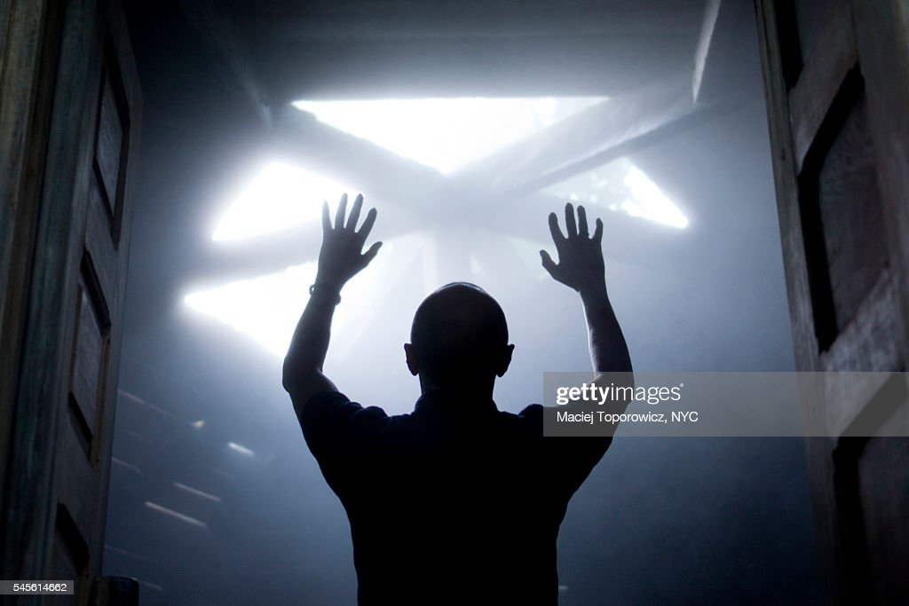 Silhouette of a man with raised hands against light coming from above. : Stock Photo