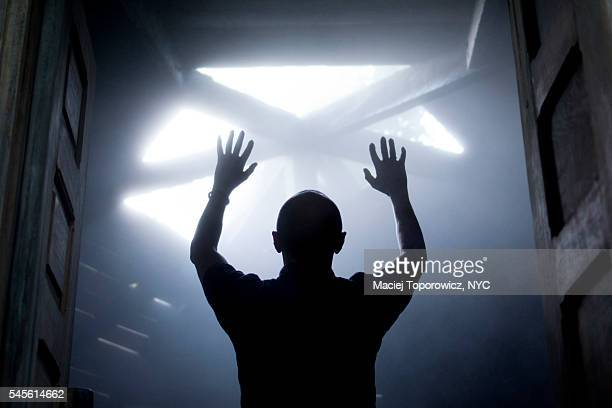 Silhouette of a man with raised hands against light coming from above.