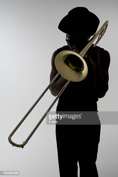 Silhouette of a man with sunglasses playing the trombone