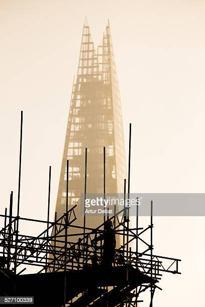 Silhouette of a man working in a building construction with the Shard London building on the background with sunset light Great Britain Europe