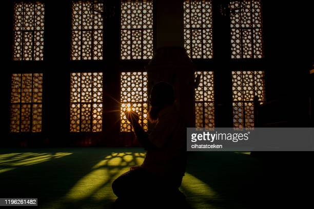silhouette of a man worshiping in mosque - islam stock pictures, royalty-free photos & images