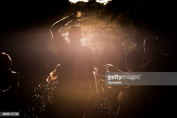 Silhouette of a marathon runner pouring water to his head during the race at sunset.