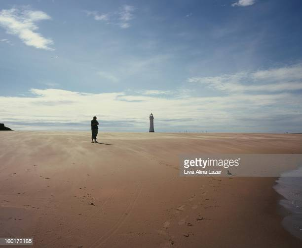 Silhouette of a meditative man on the shore; sand beach with a lighthouse. New Brighton.