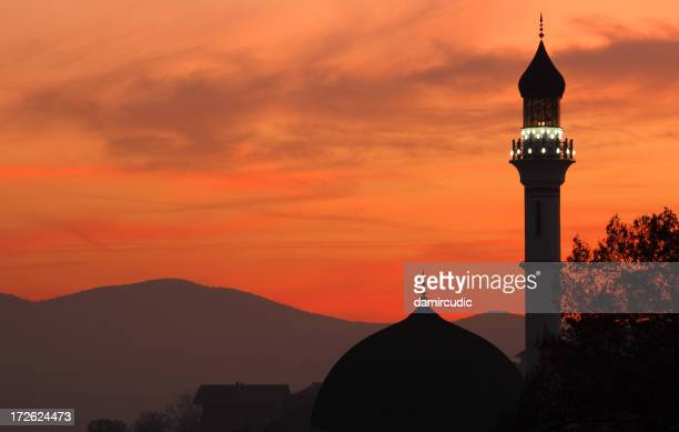 Silhouette of a mosque at dusk with an orange sky