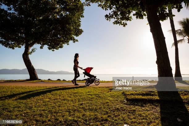 silhouette of a mother pushing a carriage at the beach - townsville australia fotografías e imágenes de stock