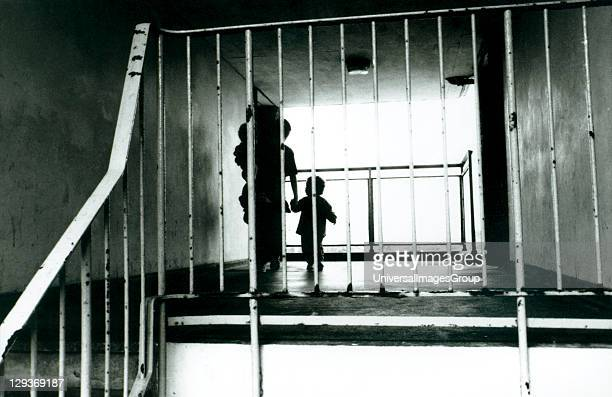 Silhouette of a mother with her children in the hallway of a block of flats on a housing estate Croydon UK 1990's