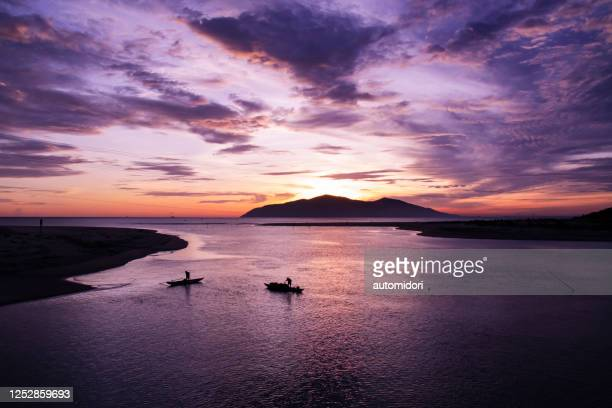 a silhouette of a mountain and two fishermen on vietnam coastline at dawn - seascape stock pictures, royalty-free photos & images