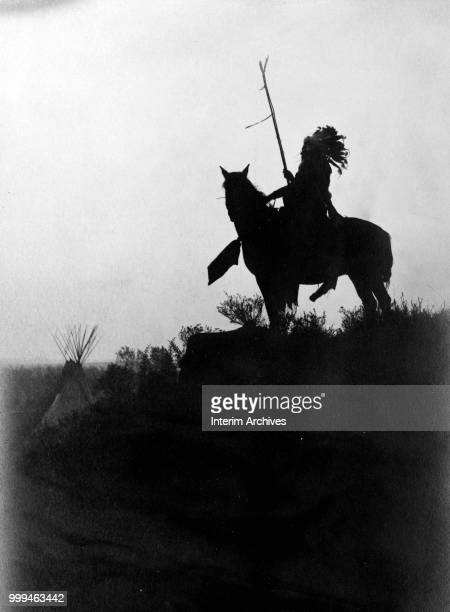 Silhouette of a Native American on horseback with a tepee in the background, circa 1907.