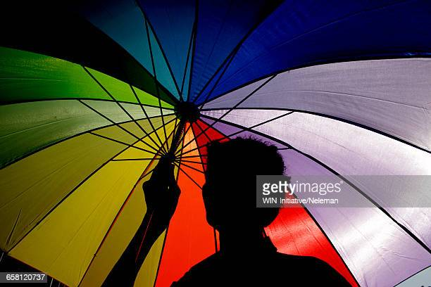 Silhouette of a person holding a multi-colored umbrella