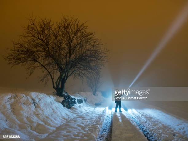 Silhouette of a person in the night, in a covered with snow field looking with a luminous lantern for the way to continuing