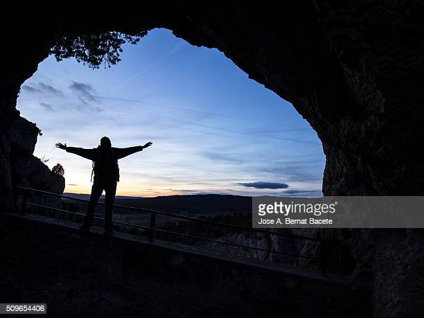 Silhouette of a person inside a cave to the dusk