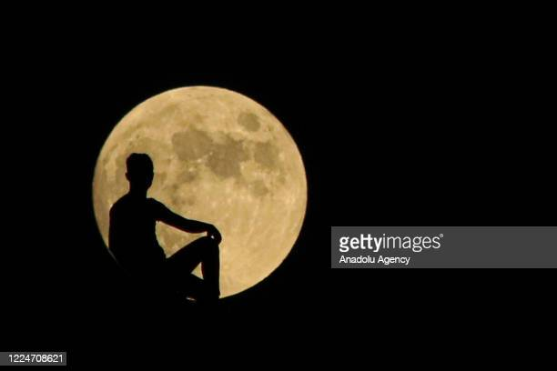 Silhouette of a person is seen in front of full moon over Darende district of Turkey's Malatya on July 04, 2020.
