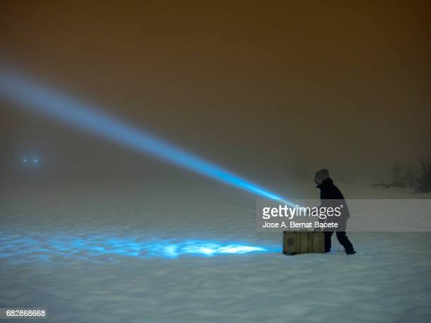 Silhouette of a person lost walking with a suitcase and a lantern, for a covered way of snow and fog during the night