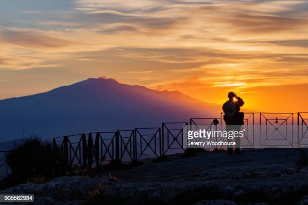 Silhouette of a person photographing mountain at sunset