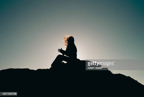 silhouette of a person sitting on cliff with hair blowing in the wind - wind stock pictures, royalty-free photos & images