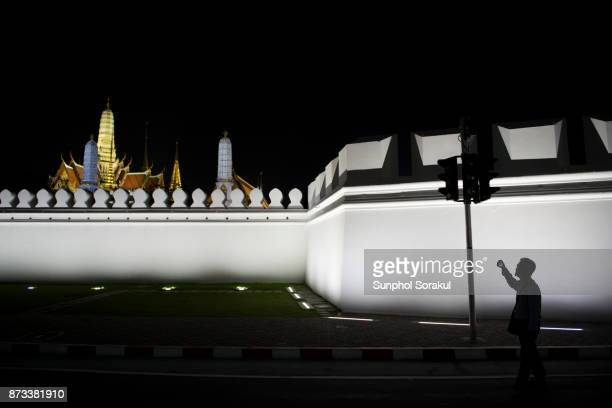 Silhouette of a person taking photography of Wat Phra Kaew at night