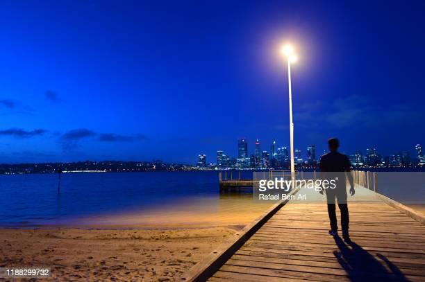 silhouette of a person walkiing on swan river bank pier against perth central business district skyline - rafael ben ari stock-fotos und bilder