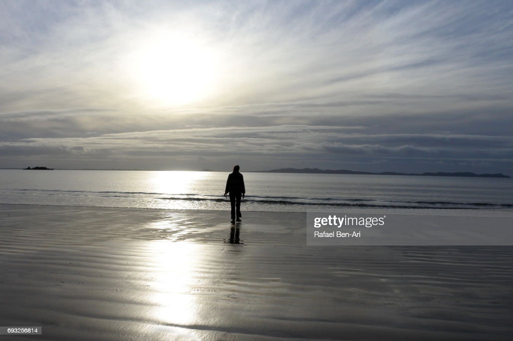 Silhouette of a person walking on a beach : Stock Photo