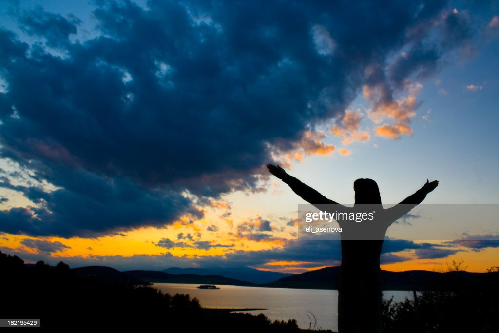 silhouette of a person with outstretched arms at sunset stock photo