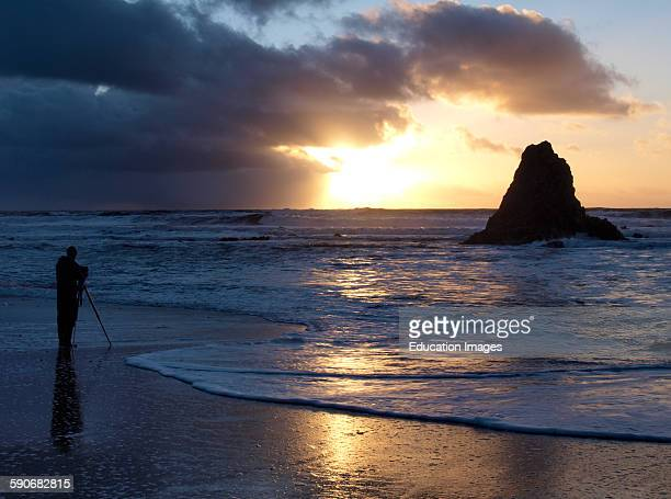 Silhouette of a Photographer at sunset Black Rock Widemouth Bay Bude Cornwall UK