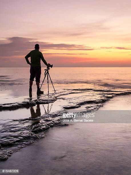 Silhouette of a Photographer on the seashore, photographing the sunrise colors