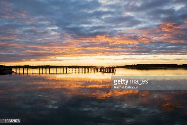 a silhouette of a pier at sunset on the intracoastal waterway on hilton head island, sc. - hilton head stock pictures, royalty-free photos & images