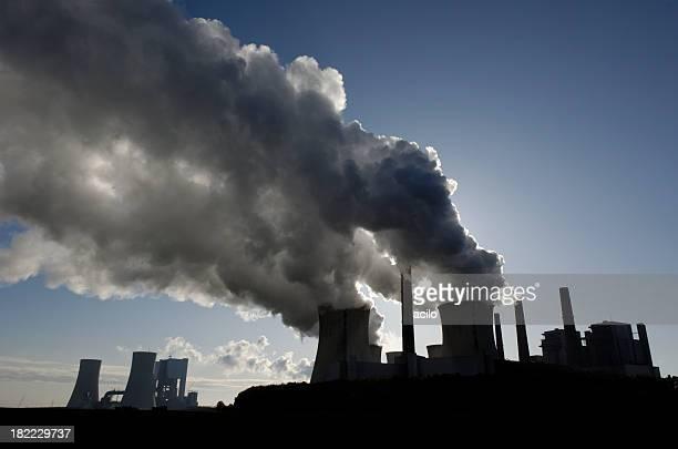 Silueta de una planta de energía con la contaminación