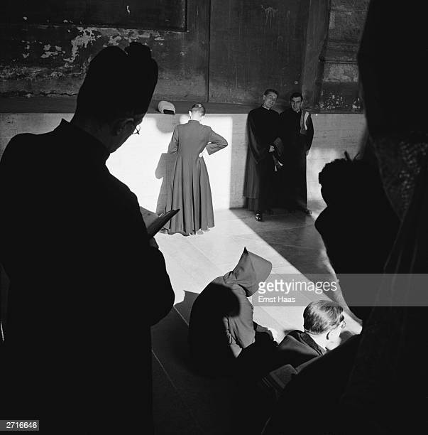 A silhouette of a priest in a biretta and a monk in a cowl are among a group of priests gathered on steps somewhere in Rome Original Publication In...