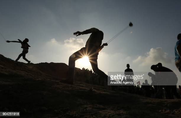 A silhouette of a protester throwing a rock with a slingshot in response to Israeli soldiers' intervention in a demonstration against US decision to...