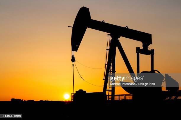 silhouette of a pumpjack at sunrise with a glowing warm sky, west of airdrie - hydrocarbon stock pictures, royalty-free photos & images