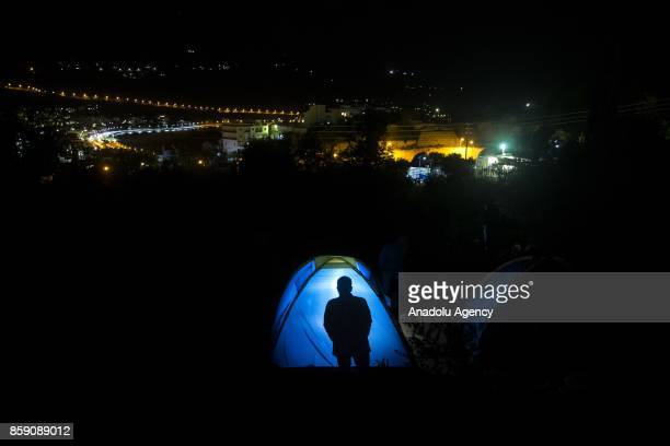A silhouette of a refugee is seen behind of a summer tent in a forestland in Samos Greece on October 8 2017 Hundreds of refugees sheltered in the...