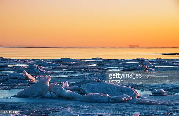 Silhouette of a remote vessel with drifting ice as foreground at sunrise