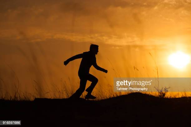 silhouette of a running boy - pakistani boys stock photos and pictures