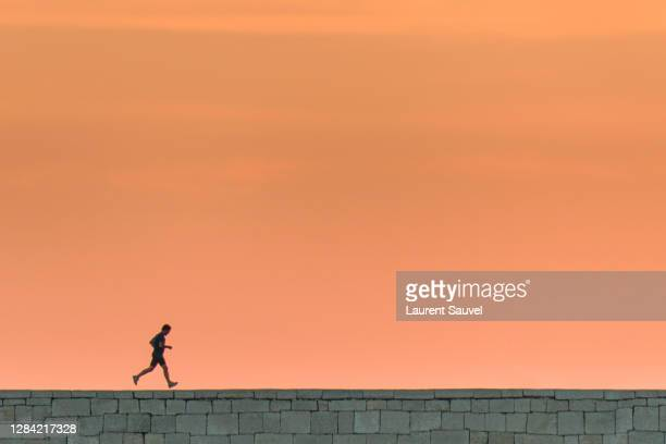 silhouette of a running man at sunset under a beautiful pink orange sky - laurent sauvel photos et images de collection